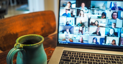 a laptop screen with many people's faces and a green coffee mug