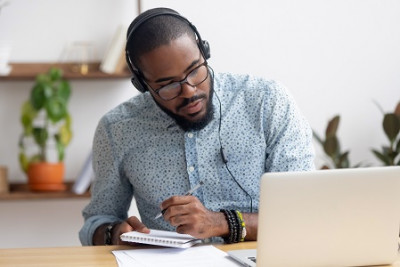 Black man wearing headphones & looking at a laptop takes notes with pen & paper