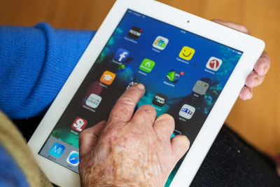 A hand hovers over an iPad with icons visible